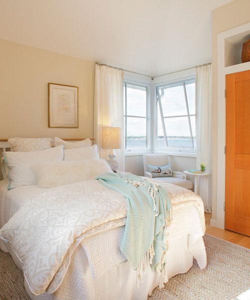 Белые шторы в интерьере спальни на берегу моря