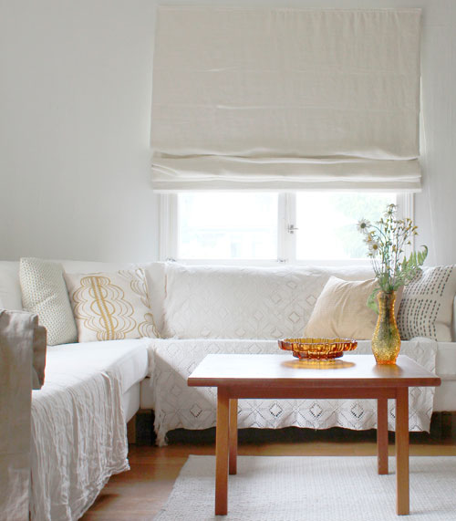 Рулонные белые шторы в интерьере гостиной