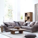 Фото 1: Серый угловой диван с подушками и деревянным столом