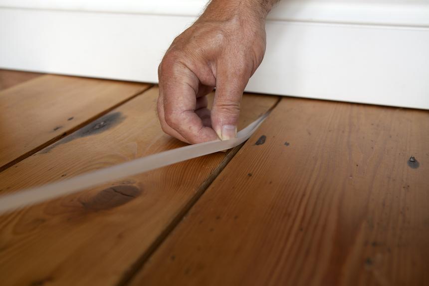 Один из методов заделки щелей в деревянном полу