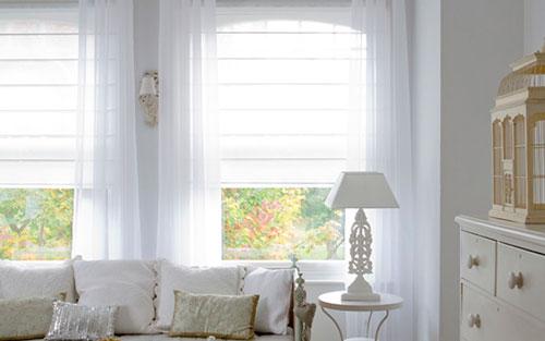 Рулонные белые шторы в интерьере светлой гостиной