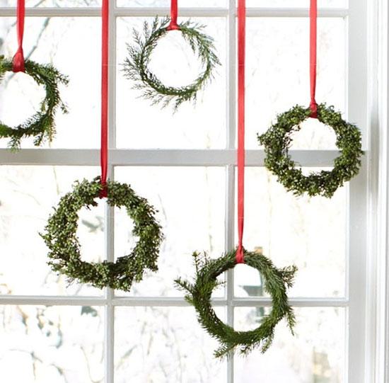 Гирлянда из еловых венков на новогоднем окне