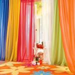 Яркая детская комната с разноцветными занавесками и ковром
