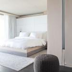 Светлая теплая нежная спальня с ворсистым ковром и необычным пуфиком