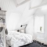 Неубранная кровать в мансардной спальне со странным грубым ковром
