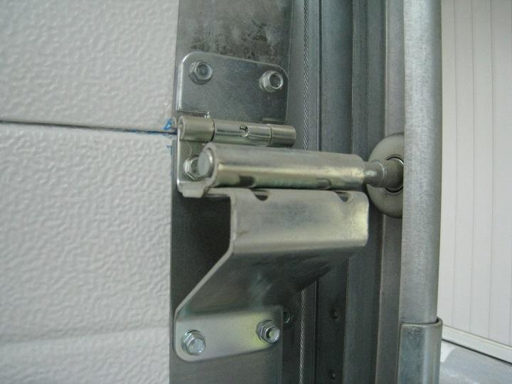 Узел крепления роликодержателя секционных ворот с шарниром секций