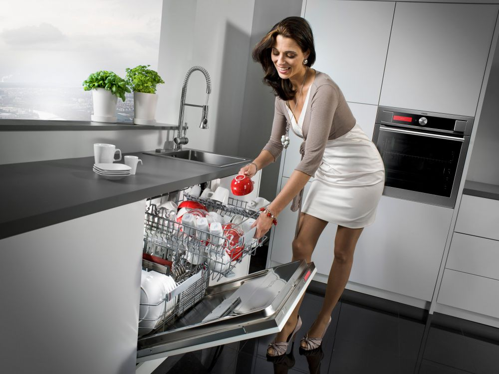 Женщина рядом с посудомойкой