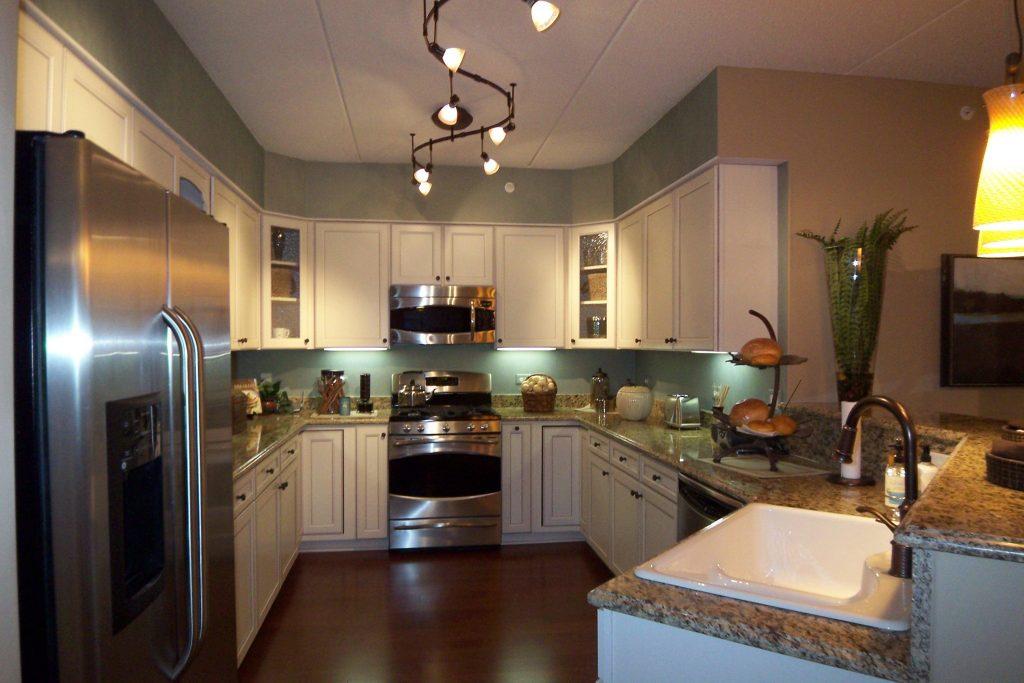 Припотолочная люстра изогнутой вытянутой формы позволяет равномерно осветить все уголки кухонного помещения